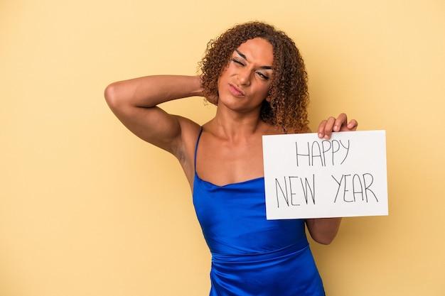 Jeune femme transsexuelle latine célébrant le nouvel an isolée sur fond jaune touchant l'arrière de la tête, pensant et faisant un choix.