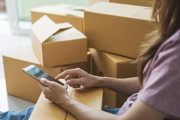 Jeune femme travaillant des affaires en ligne en utilisant un téléphone intelligent