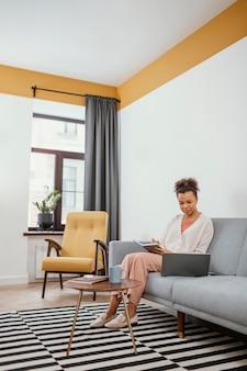 Jeune femme travaillant assis sur le canapé