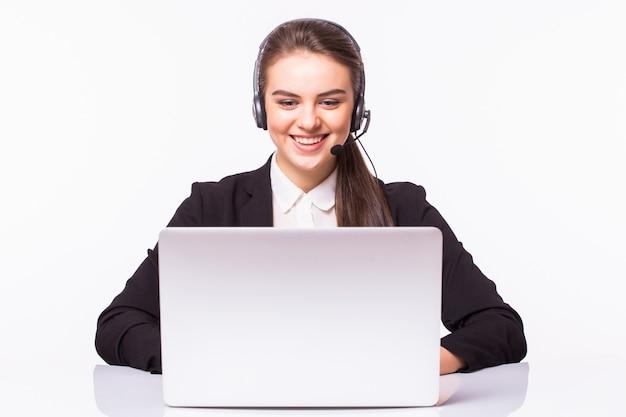 Jeune femme travaillant au bureau avec ordinateur portable et casque sur mur blanc, service client et centre d'appels.