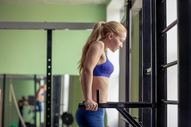 Jeune femme travaillant sur barre parallèle