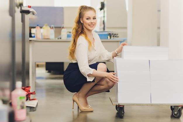 Jeune femme travaillant dans une imprimerie. presse d'imprimerie.
