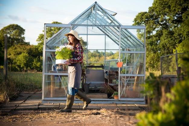 Jeune femme travaillant dans une serre en verre