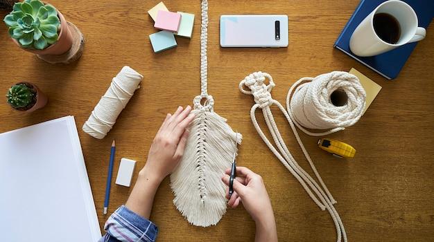 Jeune femme travaillant sur une décoration en macramé à la main