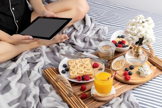 Jeune femme travaillant à domicile travaille le matin sur la tablette