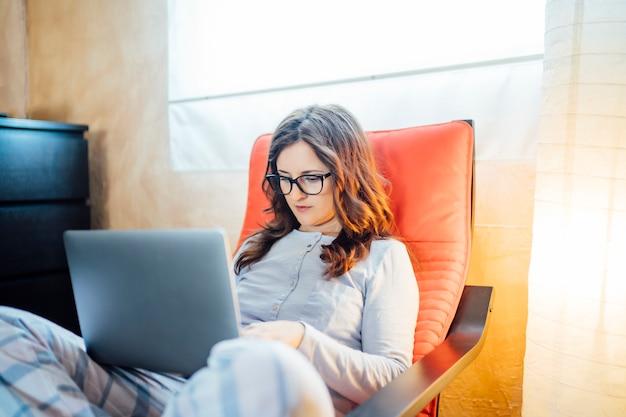 Jeune femme travaillant du lit à la maison avec ordinateur.