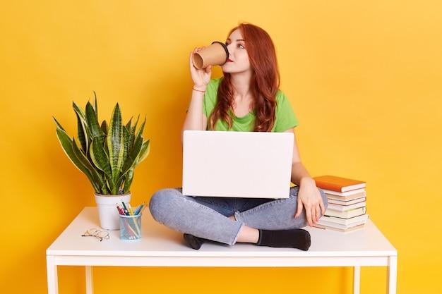 Jeune femme travaillant ou étudiant contre le mur jaune, buvant du café ou du thé, une fille au gingembre a une pause, en détournant les yeux, assise sur une table près d'un pot de fleur, pile de livres, stylos.
