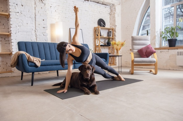 Jeune femme travaillant à la maison pendant les exercices de yoga de verrouillage avec le chien