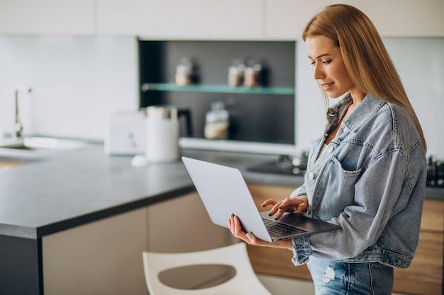 Jeune femme travaillant sur ordinateur à domicile