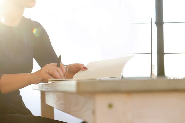 Jeune femme travaillant avec ordinateur portable et agenda