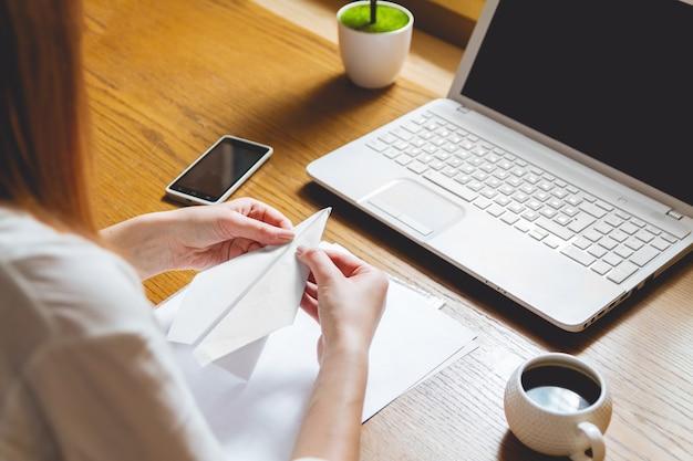 Jeune femme travaillant sur ordinateur portable assis sur le lieu de travail
