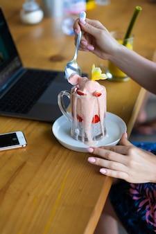 Jeune femme travaillant sur un ordinateur portable, petit-déjeuner sain avec des graines de chia et du jus.
