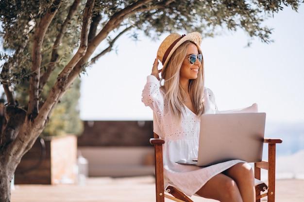 Jeune femme travaillant sur un ordinateur portable en vacances