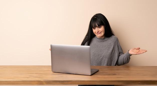 Jeune femme travaillant avec son ordinateur portable ayant des doutes tout en levant les mains