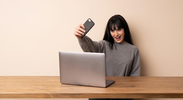 Jeune femme travaillant avec son ordinateur portable faisant un selfie