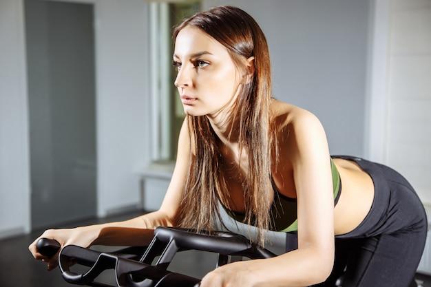 Jeune femme travaillant sur le vélo au gymnase, entraînement intense cardio.