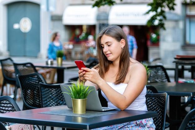 Jeune femme travaille sur ordinateur portable et à l'aide de téléphone assis dans le café de la rue, l'apprentissage à distance et le concept de travail