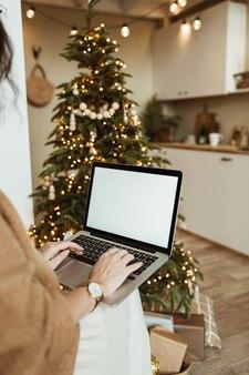 Jeune femme travaille sur un ordinateur portable avec écran d'affichage vide avec espace de copie. design d'intérieur de salon de maison moderne décoré pour la célébration de noël avec arbre de noël.