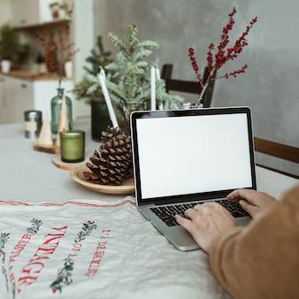 Jeune femme travaille sur un ordinateur portable avec écran d'affichage vide avec espace de copie. intérieur de cuisine avec table