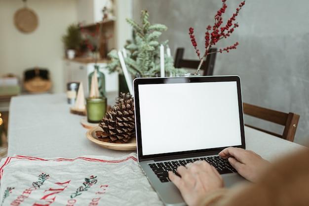 Jeune femme travaille sur un ordinateur portable avec écran d'affichage vide avec espace de copie.
