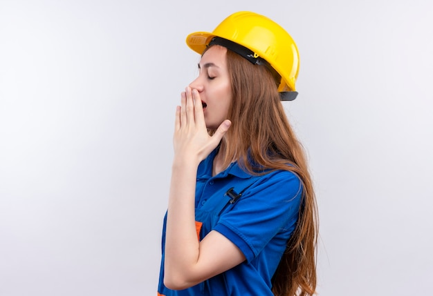 Jeune femme travailleur constructeur en uniforme de construction et casque de sécurité bâillement couvrant la bouche avec la main à la fatigue debout sur un mur blanc