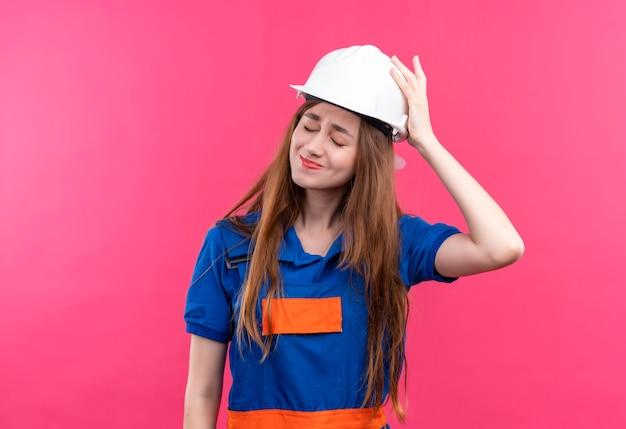 Jeune femme travailleur constructeur en uniforme de construction et casque de sécurité à la confusion avec la main sur la tête pour erreur debout sur un mur rose