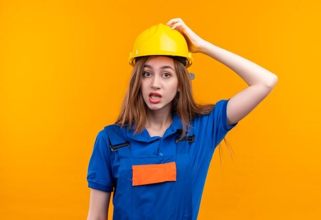 Jeune femme travailleur constructeur en uniforme de construction et casque de sécurité à la confusion de toucher le casque pour erreur debout