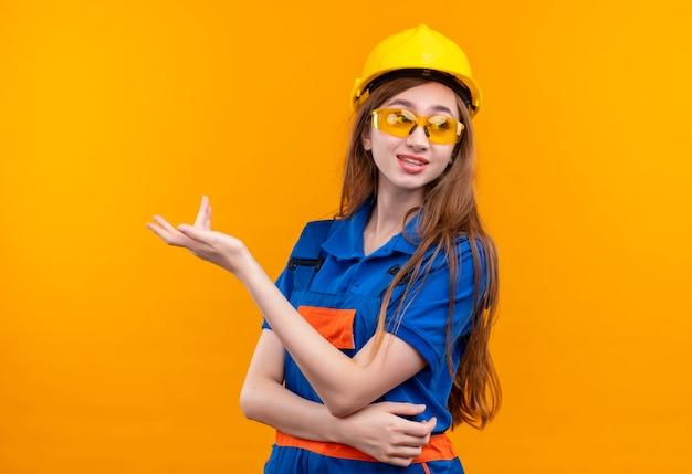 Jeune femme travailleur constructeur en uniforme de construction et casque de sécurité debout avec la main levée en faisant valoir avec une expression sceptique debout sur un mur orange