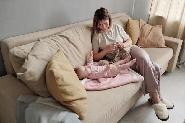 Jeune femme avec des travaux d'aiguille en regardant sa jolie petite fille