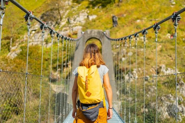 Une jeune femme traversant le pont suspendu holtzarte, larrau. dans la forêt ou jungle d'irati, au nord de la navarre en espagne et dans les pyrénées-atlantiques de france