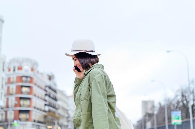 Jeune femme traversant la rue tout en tenant un smartphone