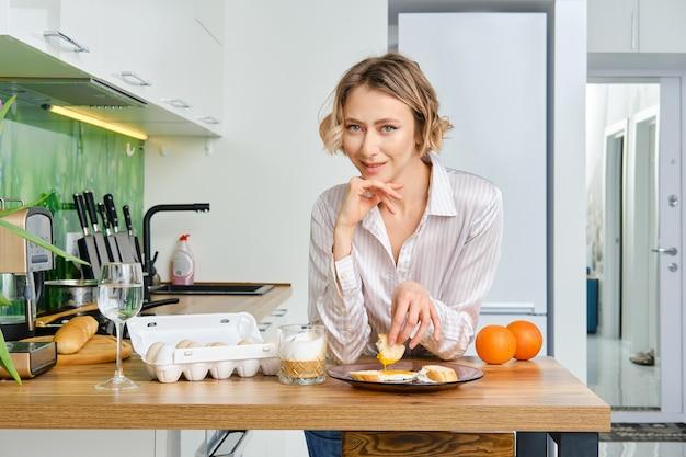 Jeune femme trempe du pain grillé dans un œuf au plat