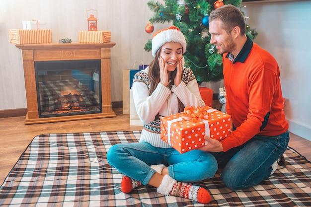 Une jeune femme très heureuse et excitée est assise sur une couverture et regarde le présent. elle garde la main sur les poussins.