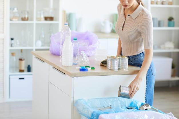 Jeune femme trier les ordures dans les différents bacs après utilisation en se tenant debout dans la cuisine à la maison
