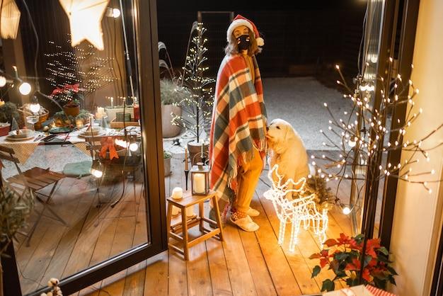 Jeune femme triste au masque facial célébrant avec un chien les vacances du nouvel an sur une terrasse à la maison. concept de quarantaine et d'auto-isolement pendant l'épidémie en vacances