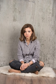 Une jeune femme triste en chemise à carreaux souffle ses joues.