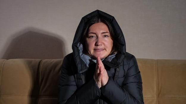 Une jeune femme triste et gelée portant une veste chaude noire avec capuche essaie de chauffer les mains assises sur un canapé moelleux dans une chambre froide sans chauffage central.