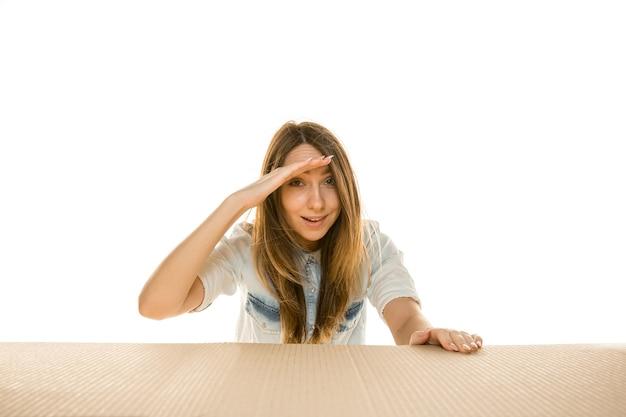 Jeune femme triste ouvrant le plus gros colis postal isolé sur blanc. modèle féminin bouleversé choqué sur le dessus de la boîte en carton regardant à l'intérieur.