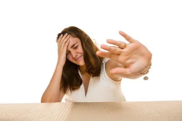 Jeune femme triste ouvrant le plus gros colis postal isolé sur blanc