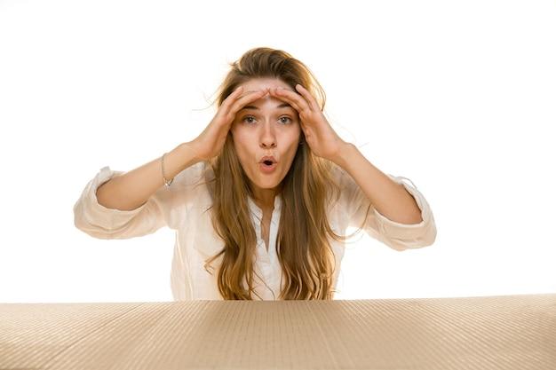 Jeune femme triste ouvrant le plus gros colis postal