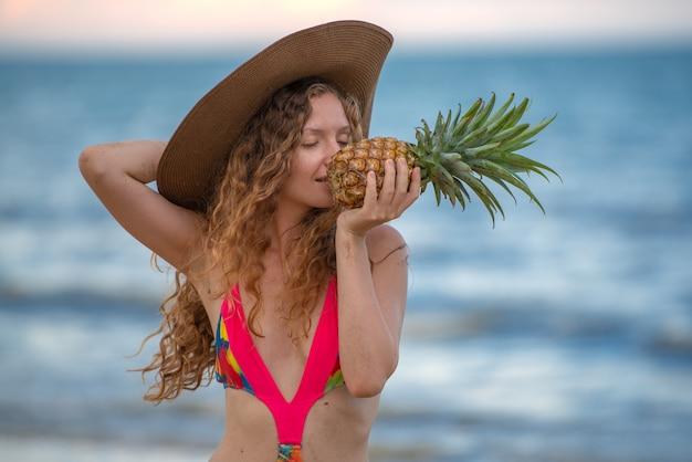 Jeune femme tropicale sexy tenant des ananas sur la plage.
