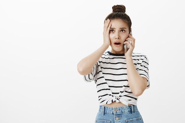 Une jeune femme troublée et inquiète reçoit de mauvaises nouvelles par téléphone mobile, debout nerveuse