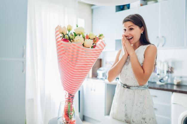 Jeune femme trouvée bouquet de fleurs dans la cuisine. heureuse fille excitée souriante