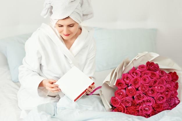 Jeune femme trouvée bouquet de roses avec des bijoux dans une boîte cadeau au lit. fille heureuse, sentant les fleurs. surprise saint valentin