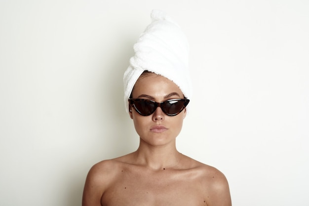 Jeune femme avec un turban serviette blanche sur la tête et des lunettes de soleil. un magnifique modèle prétentieux.