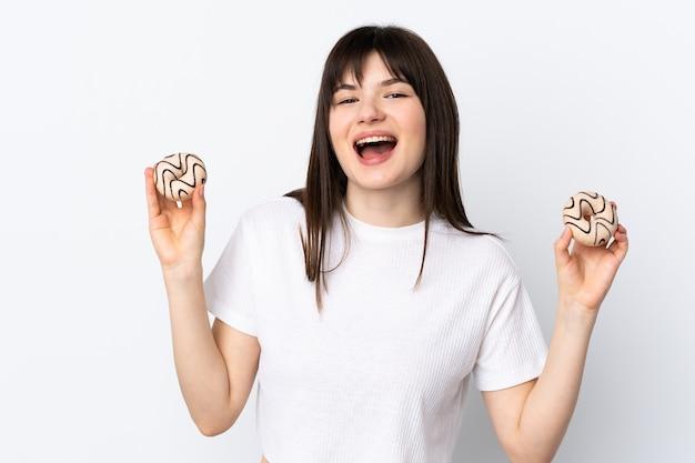 Jeune femme ukrainienne isolée sur un mur blanc tenant des beignets avec une expression heureuse