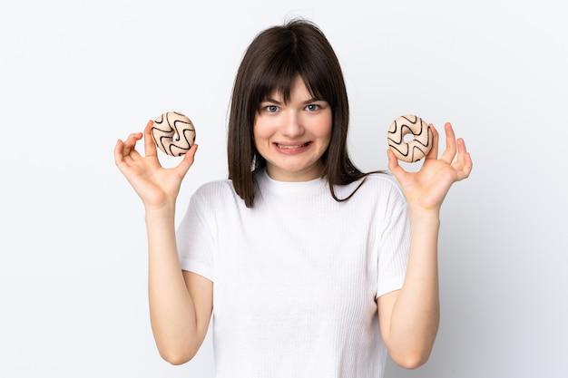 Jeune femme ukrainienne isolée sur mur blanc tenant des beignets