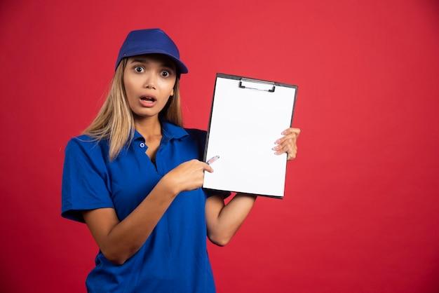 Jeune femme en uniforme bleu pointant sur le presse-papiers avec un crayon.