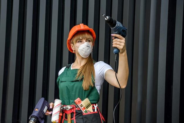 Jeune femme en uniforme et casque effectue des réparations à l'aide d'une perceuse