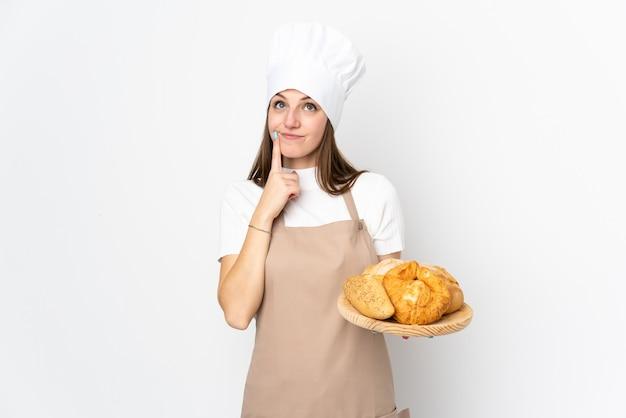 Jeune femme en uniforme de chef sur mur blanc en pensant à une idée